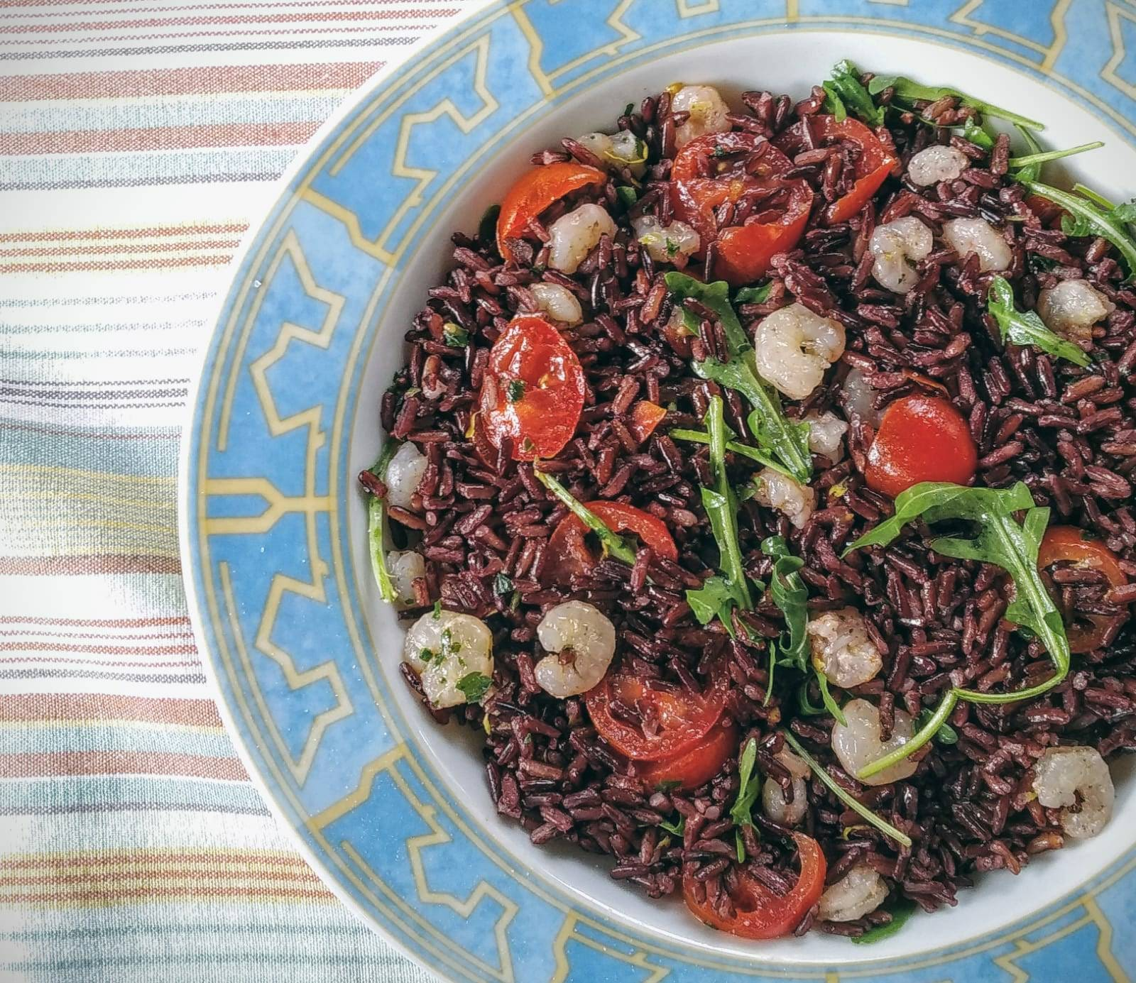 Black rice salad with rocket salad, datterini tomatoes and shrimps lime flavour